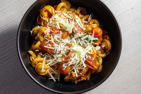 A bowl of pasta topped with shredded cheese. Standard-Bild