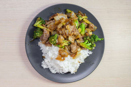 A plate of beef and broccoli stir fry with steam rice.