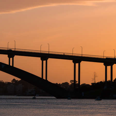 Sydney, Australia - October 8, 2021: Silhouette of a person cycling at Gladesville Bridge.