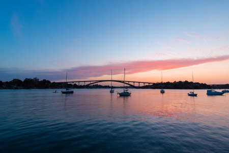Sydney, Australia - October 8, 2021: Dusk view of Gladesville Bridge with boats around.