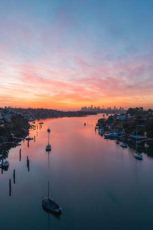 Sydney, Australia - October 9, 2021: Colorful sunrise view of Sydney skyline from Tarban Creek. Editorial