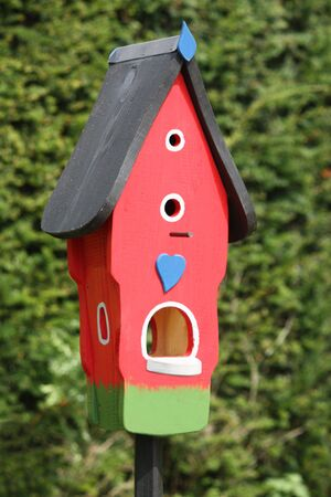 A Brightly Decorated and Colourful Wooden Bird Box. photo