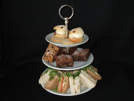 tea and biscuits: A Three Teired Plate Displaying an Afternoon Tea. Stock Photo