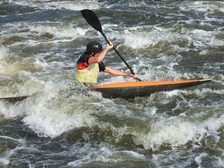 against the current: A Canoeist Paddling Against a Strong Current.