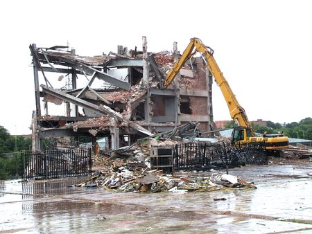 collapse: A Mechanical Excavator Demolishing an Old Building. Stock Photo
