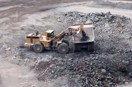 An Excavator Loading a Lorry Truck in a Granite Quarry. Stock Photo - 7354789
