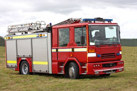 engine fire: A Fire and Rescue Vehicle Parked in a Field. Stock Photo