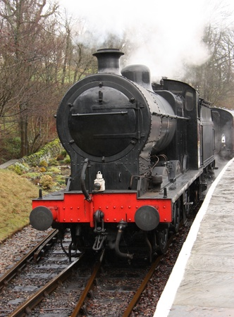 A Vintage Steam Engine Pulling Away from it s Carriages  Stock Photo - 13186839