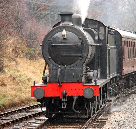 steam train: A Vintage Steam Engine Pulling Traditional Carriages. Stock Photo