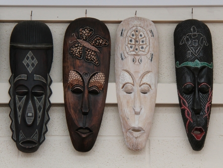 Four Different Wooden Ethnic Masks Hanging on Display. photo