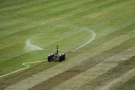 drench: A Sprinkler Watering Newly Laid Grass Turf  Stock Photo