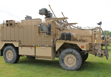 A Khaki Coloured Military Armoured Heavy Vehicle  photo