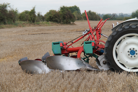 plough: A Vintage Farming Plough Pulled by an Old Tractor