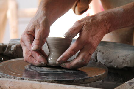 potters wheel: A Clay Pot Being Carefully Lifted from the Potters Wheel