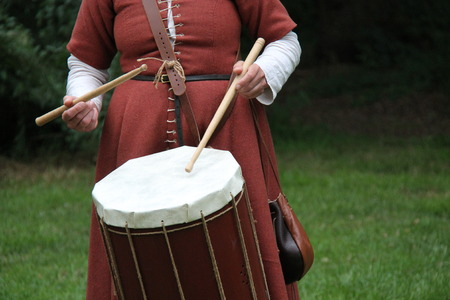 showmanship: A Lady in Costume Playing a Medieval Style Drum.