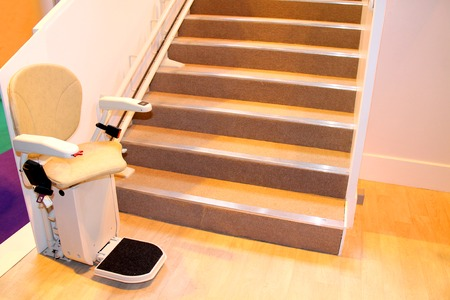 An Electric Powered Assistance Stair Lift with Seat. Stock Photo
