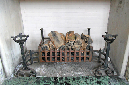A Vintage Fireplace with Wooden Logs in the Grate.