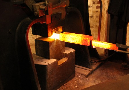 forge: The Working of Red Hot Metal in a Large Foundry Forge. Stock Photo