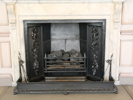 A Vintage Cast Iron Fireplace with a Black Metal Fender.