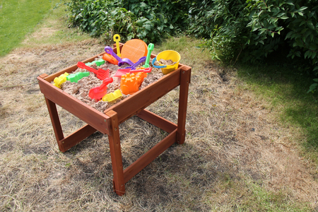 plastic toys: A Childrens Garden Sand Playpit with Plastic Toys.