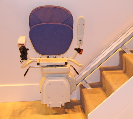 A Stair Lift in the Folded Position at the Bottom of Stairs.