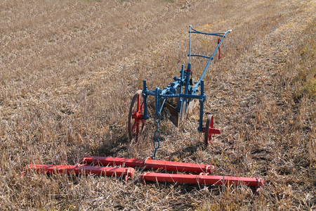 plough machine: A Hand Steered Farming Plough with a Wooden Harness.