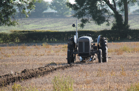 ploughing field: A Vintage Tractor Ploughing a Farmers Field.