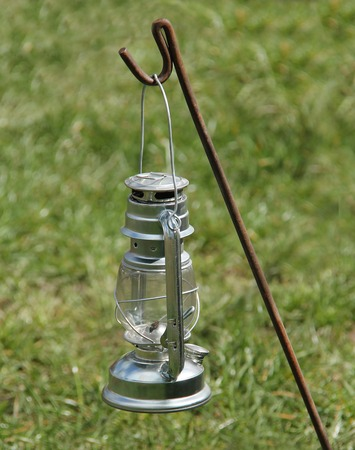 A Traditional Hurricane Lamp Hung from a Metal Stake.