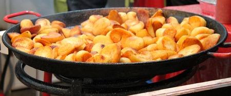 roast potatoes: A Large Outdoor Pan Cooking Roast Potatoes.