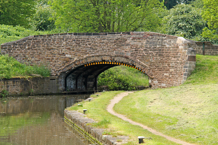 A Classic Stone Built Bridge Over a Canal and Towpath. Stock Photo