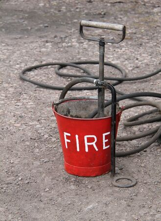 stirrup: A Vintage Fire Bucket with a Hand Operated Pump. Stock Photo