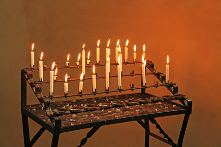 The Lit Prayer Candles in a Religious Chapel.
