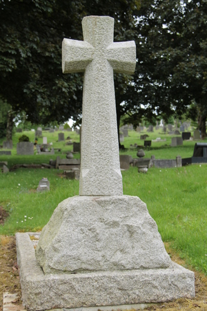 A Stone Cross on a Plinth at a Grave in a Cemetery. Stock Photo