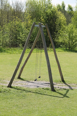 Two Childrens Play Swings on a Large Wooden A Frame. Stock Photo