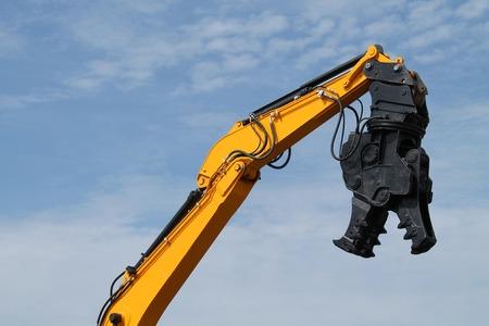 Een sloopvergruizer op een hydraulische arm van een graafmachine.