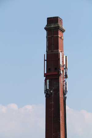 A Tall Brick Chimney with Telephone Relay Transmitters. Stok Fotoğraf