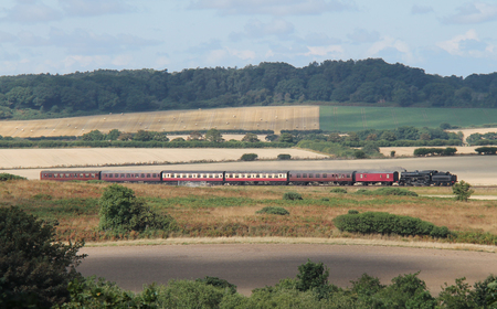 A Railway Steam Train Crossing Beautiful Countryside. Standard-Bild