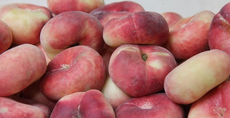 A Collection of Fresh Flat Donut Fruit Peaches.