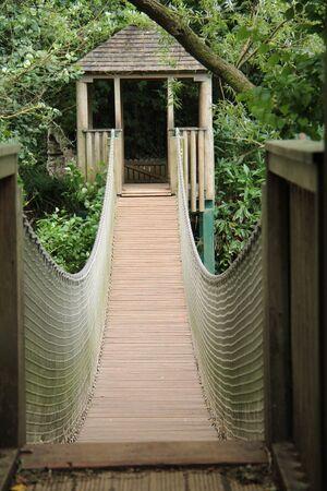 A Wooden Rope Suspended Bridge in a Woodland Area. Banco de Imagens