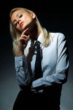Blond model, business woman pose on black background