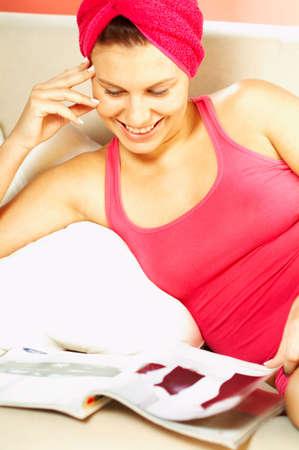 lexicon: Young pretty women reading a color magazine. Stock Photo