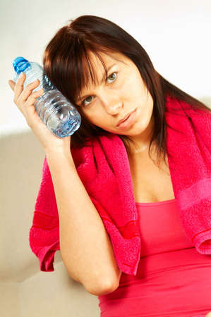 Brunette young woman with bottle of water and red towel. After fitness photo