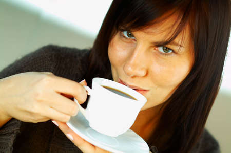 Brunette business woman with white cup of black coffee