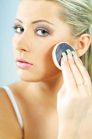 Portrait of blonde young sexy woman doing makeup photo