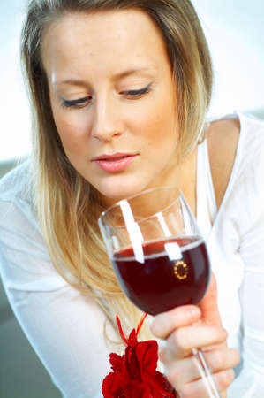 potation: Pretty young blonde women with glass of red wine