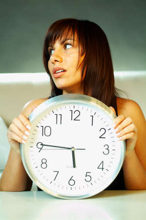 worrying: Brunette young woman with classic clock
