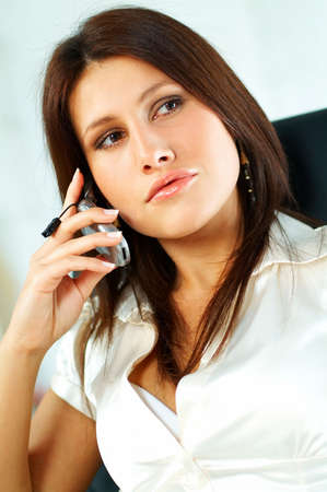 Sexy Business women talking cell phone sitting on office chair