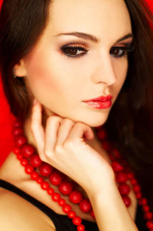 Portrait of attractive beautiful young sexy woman with black artificial eyelashes and red necklace