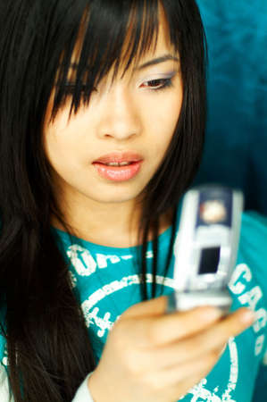 Sexy young asian girl holding cell phone photo