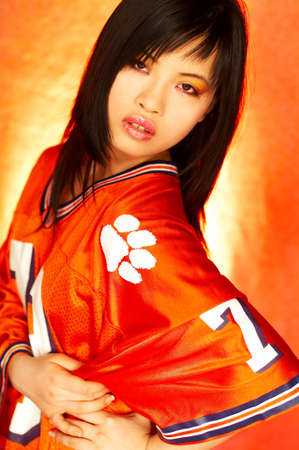 Portrait of attractive beautiful young sexy model with impressive makeup wearing orange sports football jersey photo